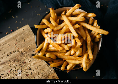 high angle shot of some appetizing french fries served in a white ceramic bowl, placed on a dark gray rustic wooden table - Stock Photo