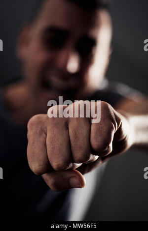 closeup of a young caucasian man throwing a punch to the observer, with a dramatic effect - Stock Photo