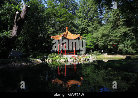 Summerhouse in Chinese style and bridge over pond in park - Stock Photo
