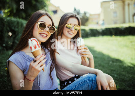 Young two women friends eat ice cream sitting on the grass in city streets - Stock Photo