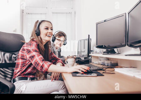 Happy colleagues working together at computer desk in office - Stock Photo