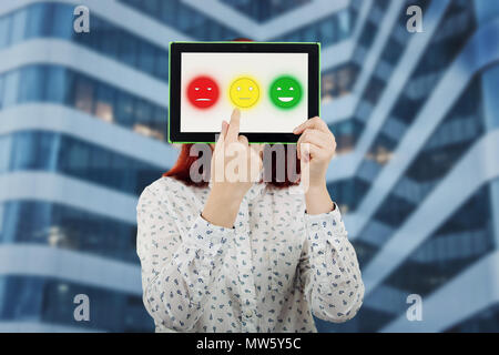 Young businesswoman covering her face using a digital tablet with three emoticons on the screen trying to choose one emotion face. Customer service ra - Stock Photo
