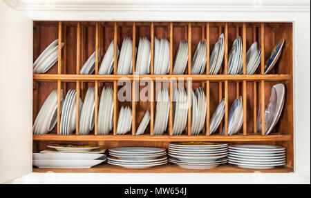 Interior of an old wooden cupboard with porcelain plates on a plate rack made with oak wood. - Stock Photo
