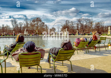 People sitting in chairs relaxing in the winter sunshine around The Grand Bassin Rond in Jardin des Tuileries ,Paris ,France - Stock Photo
