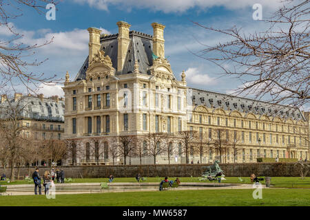 People relaxing in the winter sunshine in the Jardin des Tuileries with  Pavillon de Marsan part of the The Louvre museum in the background ,Paris - Stock Photo