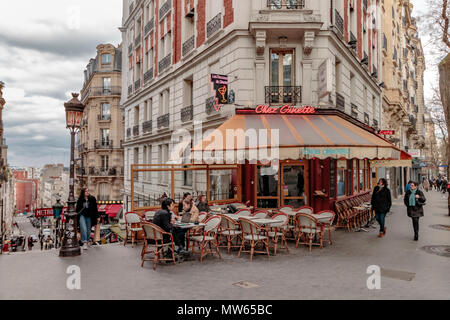 Wintertime in Paris ,people sitting outside Chez Ginette on Rue Caulaincourt, a cafe and restaurant ,Montmartre, Paris - Stock Photo