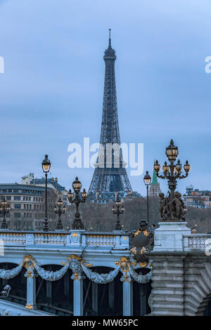Illuminated lamps at twilight on the Pont Alexandre III bridge with  The Eiffel Tower in the distance ,Paris ,France - Stock Photo
