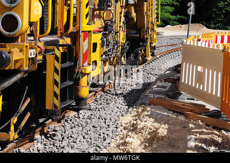 track laying machine at streetcar construction site with concrete sleepers on gravel bed - Stock Photo