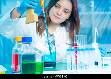 Young female tech / scientist loads liquid sample into test tube with automatic pipette. - Stock Photo