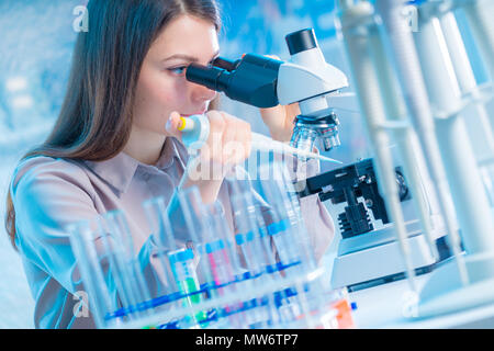 Young chemist in the laboratory. Scientist Using Microscope In Lab - Stock Photo