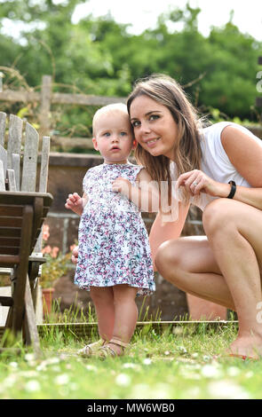 Beautiful Young baby girl toddler at 18 months old with short blonde hair with mother - model released Photograph taken by Simon Dack - Stock Photo