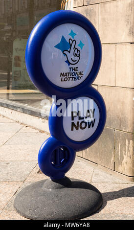 A National Lottery sign on the pavement outside a newsagents shop in Warrington Cheshire inviting people to come in and play May 2018 - Stock Photo
