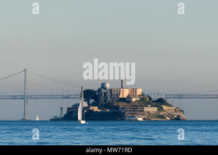 Alcatraz island with the new Bay Bridge in the background and sailboat on the water as seen from the water in San Francisco Bay - Stock Photo