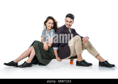 young smiling couple sitting on skateboard isolated on white - Stock Photo