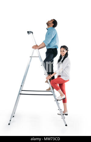 young african american couple climbing on stepladder isolated on white - Stock Photo