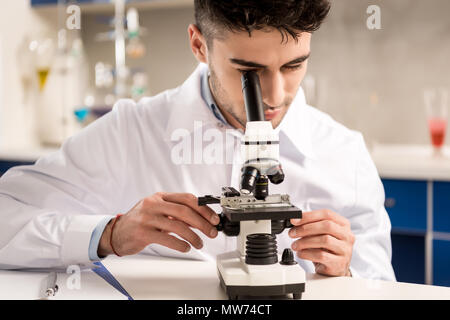 Young lab technician in white coat looking into the microscope in laboratory - Stock Photo