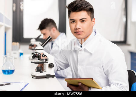 Young scientist in lab coat sitting at table in laboratory with microscope and digital tablet and looking at camera - Stock Photo