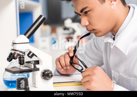 Young pensive scientist sitting at table in laboratory with microscope and test tube, while holding his glasses - Stock Photo