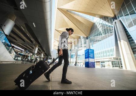 Saint-Petersburg, Russia, 21.05.2018: Stylish man traveler with baggage in Pulkovo International Airport - building exterior. - Stock Photo