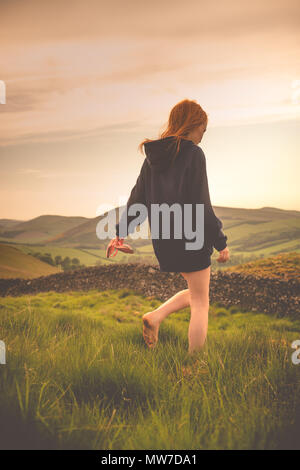 A Girl With Ginger Hair Walks with Bare Feet in a Field in the Scotttish Countryside - Stock Photo