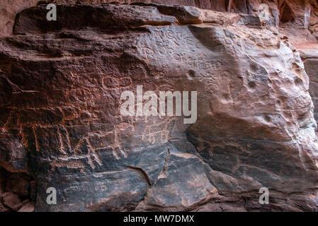 Ancient Nabatean and Thamudic inscriptions on rock representing camel caravan and humans. Khazali canyon, Wadi Rum desert, Jordan - Stock Photo