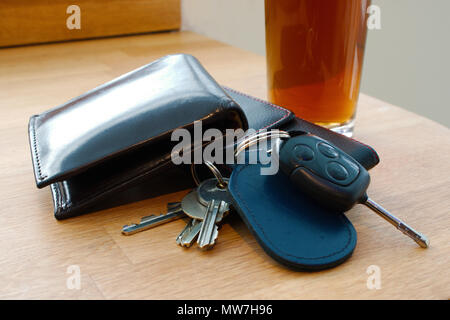Wallet, car key, house keys and mobile phone on a table together with an alcoholic beverage in the background perhaps in a pub or bar - Stock Photo