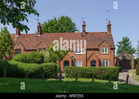 Terrace of old brick built cottages overlooking the village green, Great Brington, Northamptonshire, UK - Stock Photo