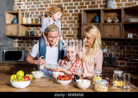 happy family with two children preparing and eating breakfast together at home - Stock Photo