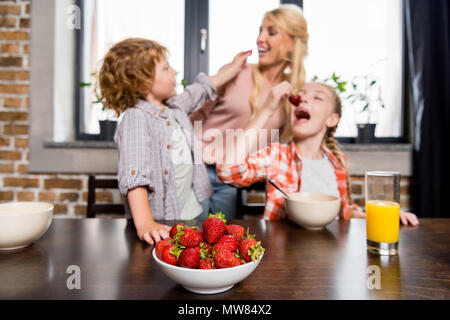 happy young mother with cute children eating strawberries at home - Stock Photo