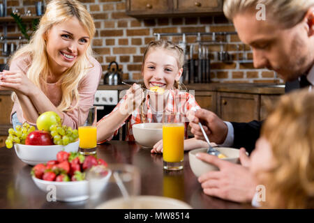 cropped shot of happy young family having breakfast together at home - Stock Photo