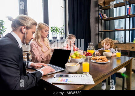 young businessman using laptop while having breakfast with family - Stock Photo