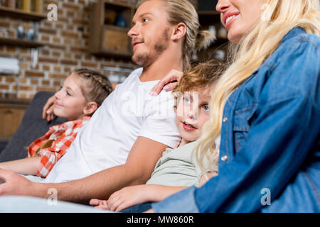 cropped shot of smiling young family watching tv together - Stock Photo