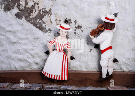 Folk dance, 3D street art of miniature cut out painted figures, attached to the weathered building exterior wall in the Riga Old Town, Riga, Latvia. - Stock Photo