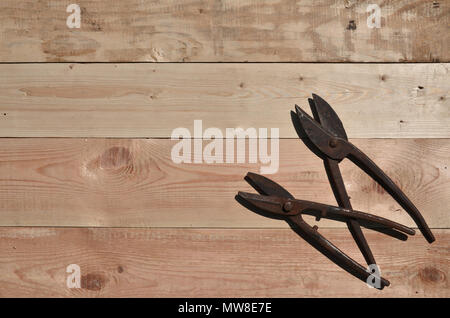 A few rusty scissors for metal on a wooden background. Obsolete household tools made of rusty metal lie on a wooden table in a workshop. The concept o - Stock Photo
