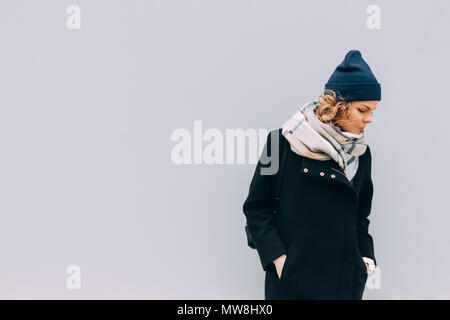 Young woman standing outdoors in cold weather on grey wall background. Female wearing coat, beanie hat and scarf, looking down, copy space. - Stock Photo