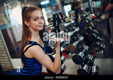 Young woman exercising biceps with dumbbells. Fitness in gym. - Stock Photo