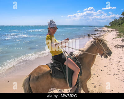 Young tourist on horseback along the coast of Parque Nacional Del Este, East National Park, Dominican Republic. Horse riding is an activity widely practiced in Bayahibe, popular tourist village. - Stock Photo