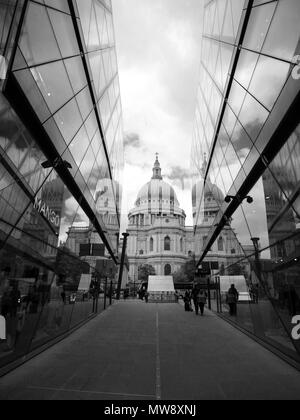 Black and white view of St Paul's Cathedral, viewed from between two glass buildings, showing the reflection of St Paul's in the glass buildings. - Stock Photo