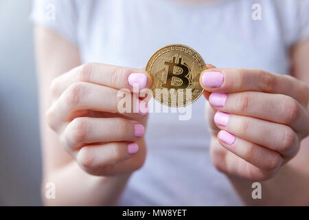 Cryptocurrency golden bitcoin coin in woman hand. Electronic virtual money for web banking and international network payment. Symbol of crypto currency - Stock Photo