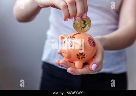 Piggy bank, woman hand holds golden bitcoin coin virtual money. Cryptocurrency and saving concept - Stock Photo