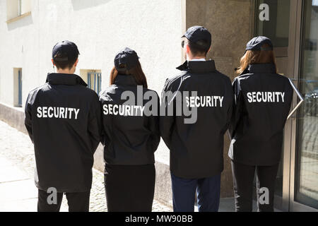 Rear View Of Security Guards Wearing Uniform Standing In A Row - Stock Photo