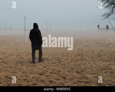 foggy cold spring day along the Chicago lakefront with volley ball poles in distance, silhouette of man walking on the beach in foreground - Stock Photo