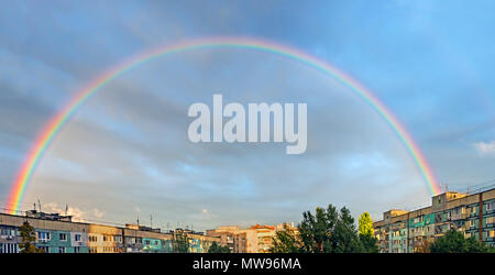 Pre-rain weather with a bright rainbow over the residential area of city - Stock Photo