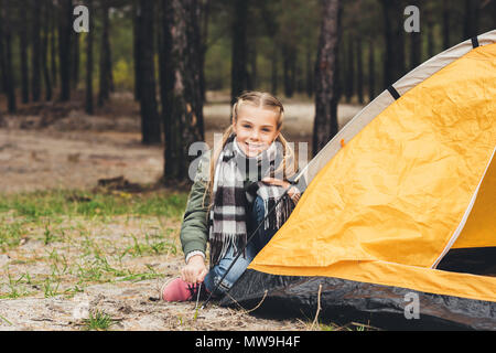 little girl installing camping tent and looking at camera - Stock Photo