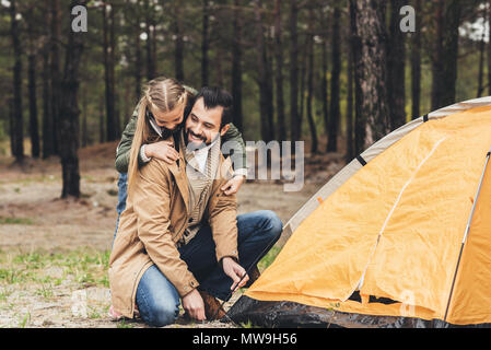 young handsome father intalling camping tent while daughter embracing him - Stock Photo