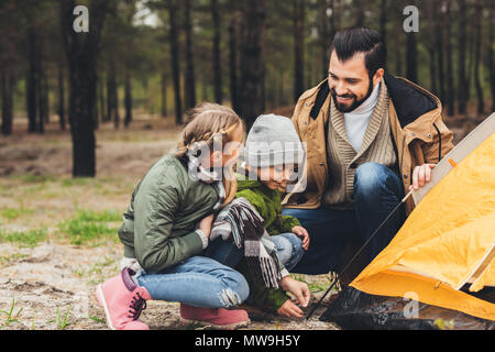 happy young father and kids installing camping tent in pine forest - Stock Photo