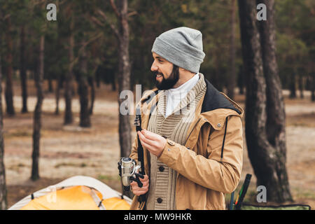 happy man having camping trip and holding fishing rod - Stock Photo