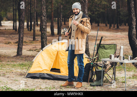 smiling young man having camping trip and holding fishing rod - Stock Photo