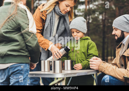 beautiful young mother pouring tea from thermos for kids on camping trip - Stock Photo