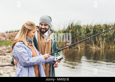 beautiful couple fishing together on cloudy day - Stock Photo